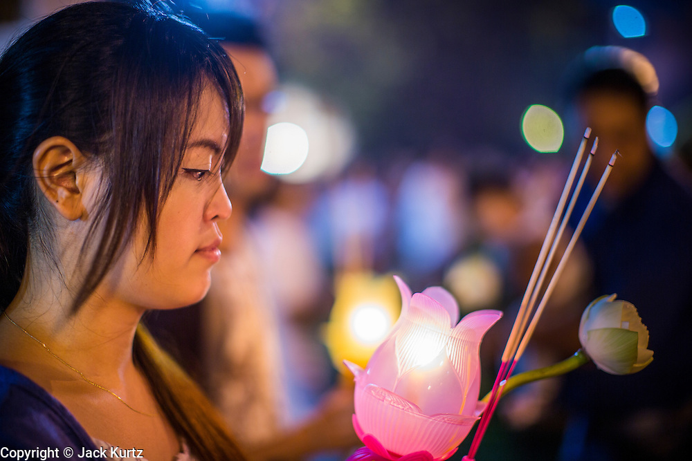 "25 FEBRUARY 2013 - BANGKOK, THAILAND:   A woman with a lantern joins a procession around Wat Benchamabophit Dusitvanaram (popularly known as either Wat Bencha or the Marble Temple) on Makha Bucha Day. Thais visit temples throughout the Kingdom on Makha Bucha Day to make merit and participate in candle light processions around the temples. Makha Bucha is a Buddhist holiday celebrated in Myanmar (Burma), Thailand, Cambodia and Laos on the full moon day of the third lunar month (February 25 in 2013). The third lunar month is known in Thai is Makha. Bucha is a Thai word meaning ""to venerate"" or ""to honor"". Makha Bucha Day is for the veneration of Buddha and his teachings on the full moon day of the third lunar month. Makha Bucha Day marks the day that 1,250 Arahata spontaneously came to see the Buddha. The Buddha in turn laid down the principles his teachings. In Thailand, this teaching has been dubbed the 'Heart of Buddhism'.    PHOTO BY JACK KURTZ"