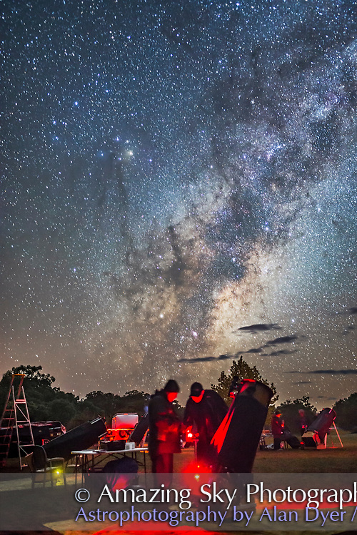 Observers at the 2017 OzSky Star Party in Australia check their charts for hunting down targets with one of the large Dobsonian telescopes at the Warrumbungles Motel site. The centre of the Galaxy rises behind them.