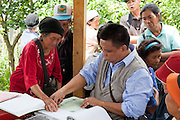Villagers gather as a government official takes thumbprints (due to illiteracy) of an elderly woman for the Malaysia census 2010 Nabalu, Sabah