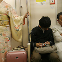 Two commuters sleep whilst a woman in a kimono stands,  Tokyo, Japan.
