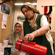 Lailoma Dost (right) pours tea after working all morning with a fellow Afghan refugee who came to Canada as a refugee two  years previously. Lailoma works at a government building where she works five days a week  as a cleaning lady.  Photo by Louie Palu/The Globe and Mail ©
