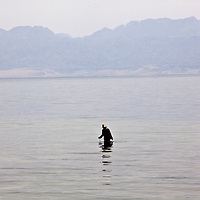"A woman searches for octopus outside of Dahab, Egypt. The Blue Hole is notorious for the number of diving fatalities which have occurred there, earning it the sobriquet ""World's Most Dangerous Dive Site"" and the nickname ""Diver's Cemetery"". The site is signposted by a sign that says ""Blue hole: Easy entry"". Accidents are frequently caused when divers attempt to find the tunnel through the reef (known as ""The Arch"") connecting the Blue Hole and open water at about 52 m depth. According to dive experts roughly 10 people die each year. April 2012."