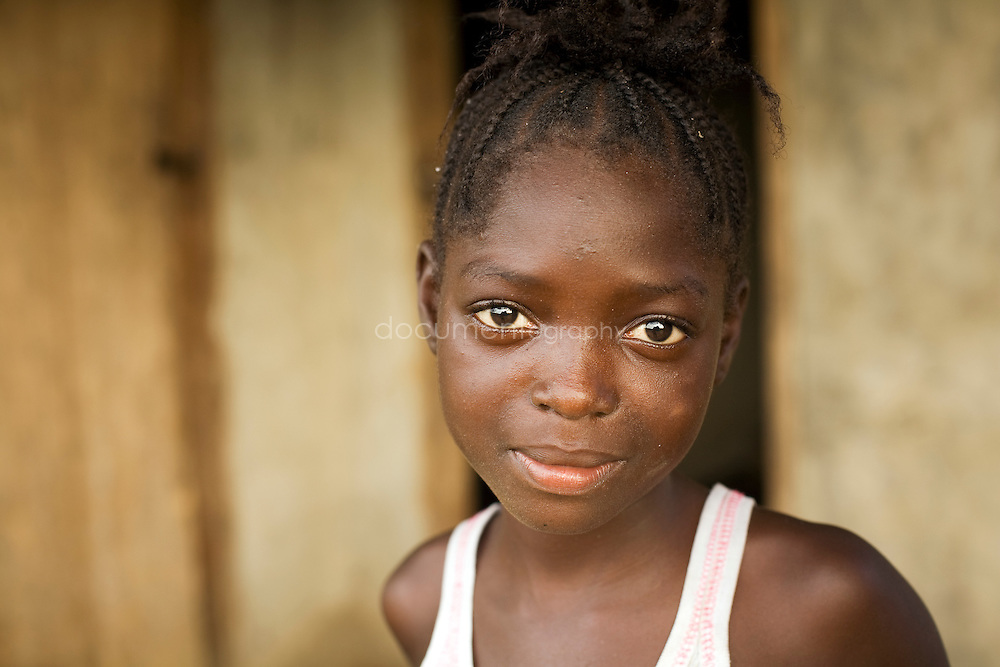A girl in front of her home, Kingsville #7, Liberia.
