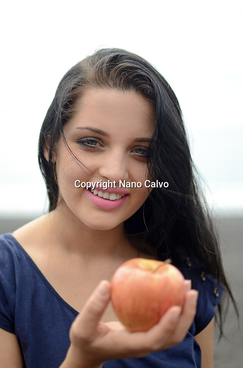 Cute brunette holding a red apple on the beach