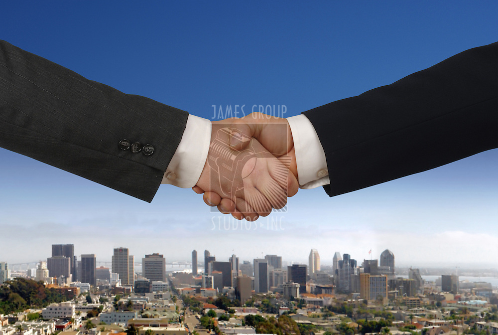 Two businessmen shaking hands with daytime city skyline in the background