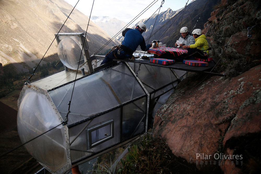 A guide (L) serves breakfast to guests above the cabine at the Skylodge Adventure Suites in the Sacred Valley in Cuzco, Peru, August 14, 2015. The Skylodge is composed by three capsule suites hanging at the top of the 1300 feet mountain with a 300 degree view of the Valley. To sleep at Skylodge, people must climb 400 meters of Via Ferrata path and to leave the hotel people go down  a trail through ziplines. REUTERS/Pilar Olivares