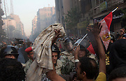 """Protestors wave an Egyptian flag stained with blood as they confront the Egyptian military during a moment of a cease fire between the protestors and Egyptian military. A crowd of tens of thousands filled Cairo's Tahrir Square Tuesday, answering the call for a million people to turn out and intensify pressure on Egypt's military leaders to hand over power to a civilian government. The ruling military council held crisis talks with political parties across the spectrum to try to defuse growing cries for a """"second revolution.""""(Photo by Heidi Levine/Sipa Press)."""