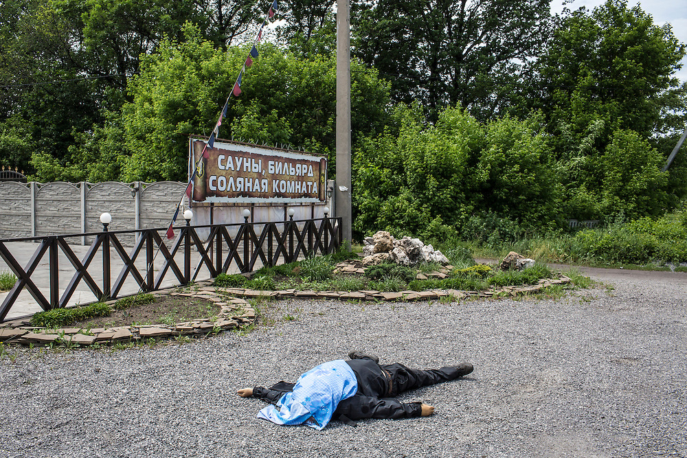 KARLIVKA, UKRAINE - MAY 23: The body of a pro-Ukraine militia fighter lies along the road following early morning clashes with the Vostok Battalion, a pro-Russia militia, on May 23, 2014 in Karlivka, Ukraine. At least eight people between the two sides, including one civilian, were killed in an early morning firefight when the Donbass Battalion, a pro-Ukraine militia, attacked a Vostok Battalion checkpoint in the nearby town of Karlivka. (Photo by Brendan Hoffman/Getty Images) *** Local Caption ***
