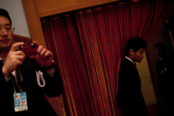 A man takes pictures as Chinese security officers guards the entrance to the audience seats during the opening session of the National Peoples Congress (NPC) in the Great Hall of the People in Beijing, China, on 05 March 2011. The NPC has over 3,000 delegates and is the world's largest parliament or legislative assembly though its function is largely as a formal seal of approval for the policies fixed by the leaders of the Chinese Communist Party.