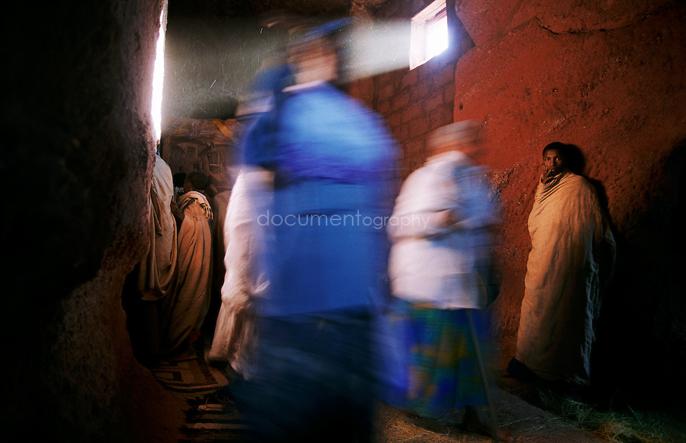Pilgrims gather to look at a painting in Bet Golgotha. They also collect ashes in each church, which they mix with water and drink as a medicine. Every church in Lalibela has its specific cross, and the pilgrims seek to be blessed in every church.