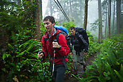 Zach Podell-Eberhardt (left) and Henry Pedersen hike through a damp, misty forest along the West Coast Trail, British Columbia, Canada.