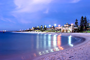 On a perfectly still night the lights from the Indiana restaurant reflect across the swimming area of Cottesloe Beach with a blue sky almost matching the water.