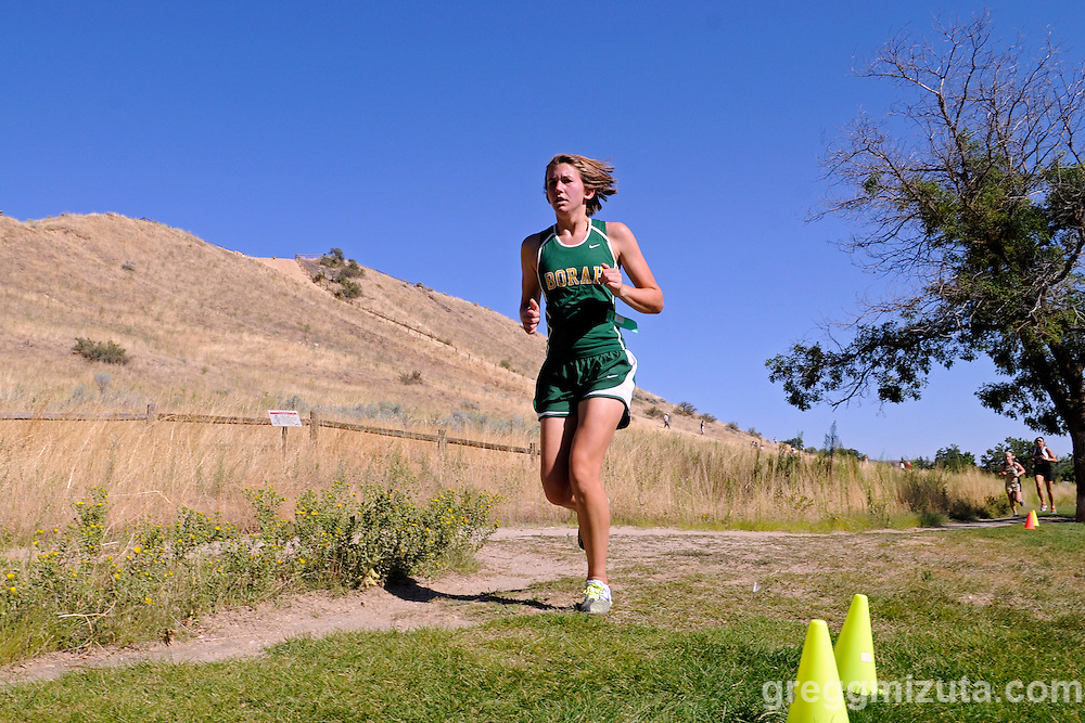 Borah junior Sarah Ash comes off the single track with the Camel's Back foothills in the background during the Camel's Back Invitational in Boise, Idaho on August 27, 2010. in the background. Ash finished in 26:39.34, almost three minutes faster than she ran in this meet last year.