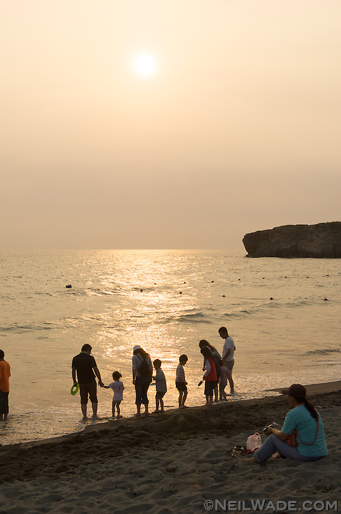 A family plays in the ocean waves on Cijin Island, Kaohsiung, Taiwan.