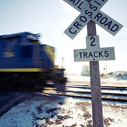 A train speeds through a rural crossing protected by simple crossbuck signs.