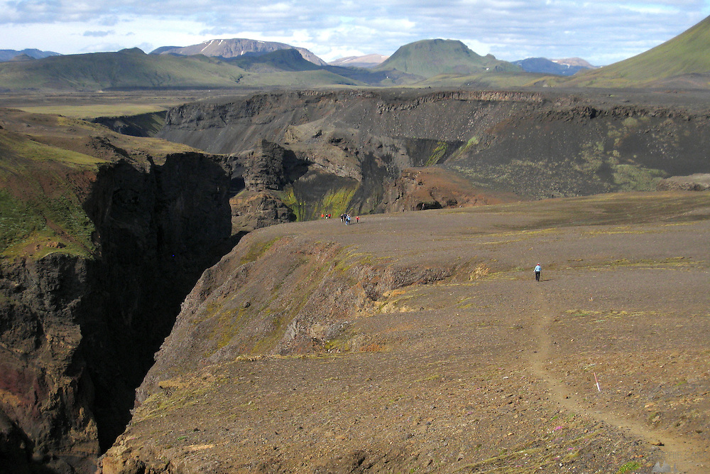 A woman hikes towards the edge of a deep canyon near the huts at Emstrur, along the Laugavegur Trail in southern Iceland.