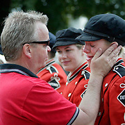 """MOC Floyd-Valley band director Steve Connell, left, comforts senior band member Stacie Oolman after the Pride of the Dutchmen Marching Band's last march in the Orange City Tulip Festival.  Connell said goodbye to 36 seniors, all of whom have been in the band since their freshmen year.  """"I love you all,"""" Connell told his seniors before their final march through Orange City's main street.  """"I can't remember my wife's birthday, but if I see any of you in the future, I'll remember your name and what instrument you played.""""  The Pride of the Dutchmen Marching Band is one of the most successful competition bands in the state, and have marched in cities all over the country."""