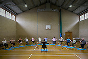 A group of senior citizens learn Yoga at a north London day centre. .Yoga is a form of exercise that adapts to your needs and abilities, which makes it suitable for the elderly. It makes your body fitter, the mind calmer and more relaxed. Yoga is also beneficial in the prevention and control of common health and emotional problems that is linked with Old Age