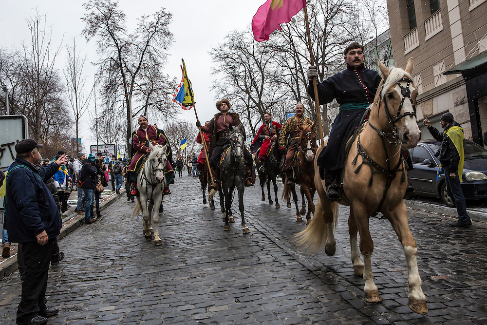 KIEV, UKRAINE - DECEMBER 8: Men dressed as Cossacks ride horses through the streets on December 8, 2013 in Kiev, Ukraine. Thousands of people have been protesting against the government since a decision by Ukrainian president Viktor Yanukovych to suspend a trade and partnership agreement with the European Union in favor of incentives from Russia. (Photo by Brendan Hoffman/Getty Images) *** Local Caption ***