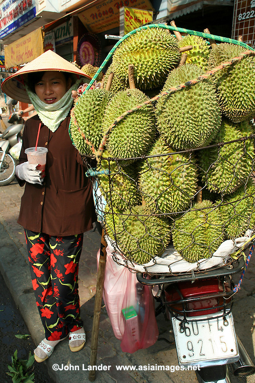 """Durian Vendor, Ben Thanh Market - Widely known and appreciated in southeast Asia as the """"king of fruits the durian is distinctive for its large size, unique odour and formidable thorn covered husk.  The edible flesh emits a distinctive smell, strong and penetrating even when the husk is intact. Some people regard the durian as fragrant; others find the aroma overpowering and offensive - the smell evokes reactions from deep appreciation to intense disgust. The odour has led to the fruit's banishment from hotels and public transportation in southeast Asia."""