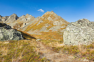 Boulders from erosion of the rugged Talkeetna Mountains lay scattered in Archangel Valley at Hatcher Pass in Southcentral Alaska. Afternoon. Autumn.