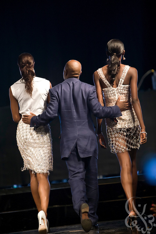 "Acclaimed fashion designer Chris Aire is escorted out onto the runway by Nigerian model Oluchi (r) during his show in support of the July 13, 2008 leg of the ThisDay music and fashion festival in Lagos, Nigeria. The festival, themed ""Africa Rising"", aims to raise awareness of African issues while promoting positive images of Africa using music, fashion and culture in a series of concerts and events in Nigeria, the United States and the United Kingdom. ."