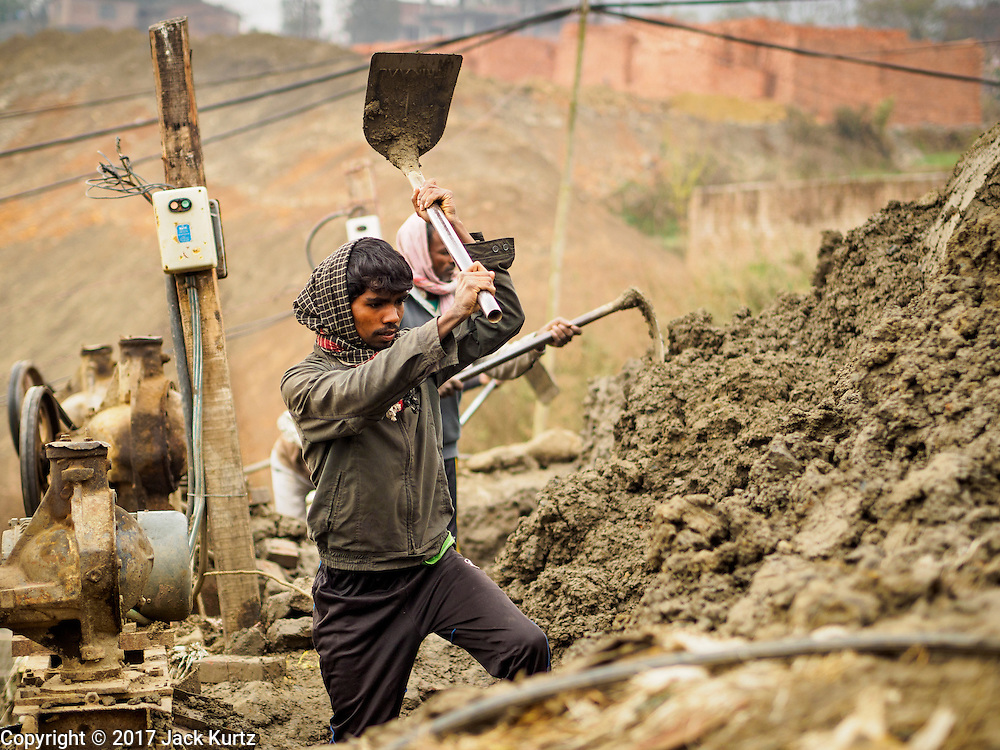 03 MARCH 2017 - BAGMATI, NEPAL: A workers uses a hoe to hack clay out of hillside to make bricks at a brick factory in Bagmati, near Bhaktapur. There are almost 50 brick factories in the valley near Bagmati. The brick makers are very busy making bricks for the reconstruction of Kathmandu, Bhaktapur and other cities in the Kathmandu valley that were badly damaged by the 2015 Nepal Earthquake. The brick factories have been in the Bagmati area for centuries because the local clay is a popular raw material for the bricks. Most of the workers in the brick factories are migrant workers from southern Nepal.       PHOTO BY JACK KURTZ