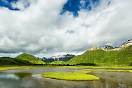 Lush green vegetation contrasts with the remnant snows of winter on the mountains surrounding this pond near Pasagshak on Kodiak Island in Southwestern Alaska. Summer. Afternoon.