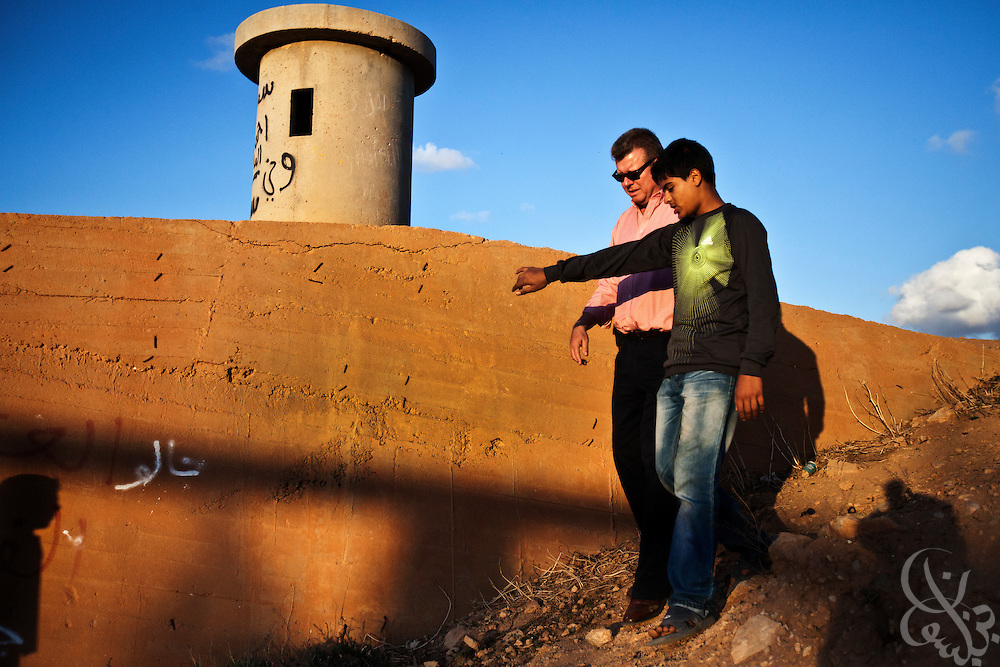 Dr. Ronald Meinardus (l), Regional Director of the Friedrich Naumann Foundation for Liberty (FNF) speaks with a Libyan teenager as he tours a former bunker at a looted and destroyed military base in  Benghazi, Libya December 16, 2011. Before it was overrun in the first days of the revolution, the base once stood as the city's central garrison for troops and authorities loyal to former leader Muammar Gaddafi. (Photo by Scott Nelson, for Der Spiegel)