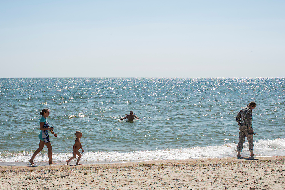 MELEKYNE, UKRAINE - AUGUST 30, 2015: A woman and small boy walk past as fighters from the Donbass Battalion, a pro-Ukraine militia that has been integrated into the National Guard, visit the beach near their base in Melekyne, Ukraine. Many of the formerly autonomous battalions have recently been pulled back from the front line and replaced by regular Ukrainian soldiers, which has frustrated some of the fighters, who consider themselves battle-tested and eager to continue the fight. CREDIT: Brendan Hoffman for The New York Times