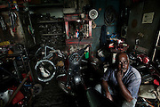 Mauritius. Mr. Campbell, in his motorbike workshop. Chinatown. Port Louis.