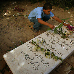 A young Palestinian visits the grave of Yasser Arafat's sister, Anam, in Khan Yunis, Palestinian Territories, Nov. 9, 2004. Arafat was diagnosed with liver failure while in critical condition in a Paris hospital.