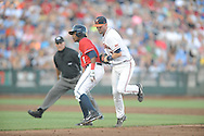 Mississippi's Errol Robinson (6) is tagged out by Virginia's Branden Cogswell (7) on a missed hit and run in the College World Series in Omaha, Neb. on Sunday, June 15, 2014. Virginia won 2-1.