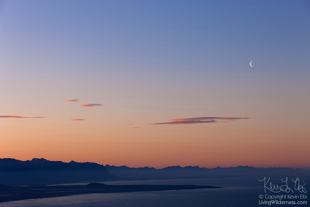 The crescent moon is visible over the mountain range at the center of Snæfellsnes, a scenic peninsula in western Iceland.