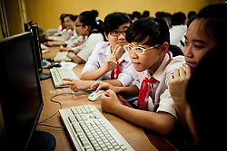 Group of students facing a computer, Hanoi, Vietnam, Southeast Asia