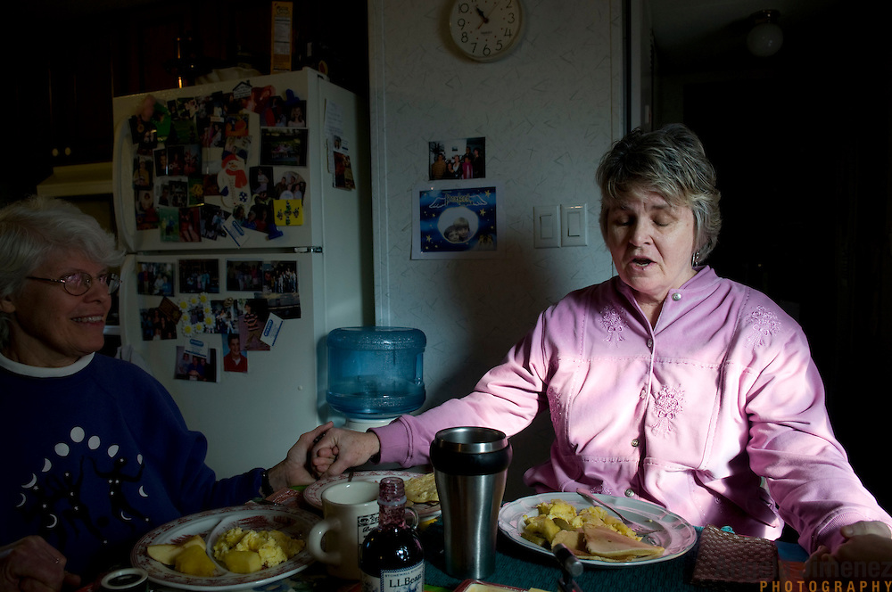 "Date: 1/09/09.Desk: STL.Slug: WOMYN.Assign ID: 30074969A..Morgana MacVicar, 61, right, says a prayer before breakfast at another resident's home at Alapine, a ""womyn's land"" or lesbian intentional community, in rural northeast Alabama. At left is Emily Greene, 62. ..(*the exact town/location of the community cannot be revealed in the caption or article, per agreement with the subjects)..Photo by Angela Jimenez for The New York Times .photographer contact 917-586-0916"