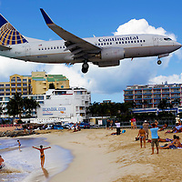 St. Martin St. Maarten -- February 2011 -- Sunbathers watch an Continental Airlines plane land over Maho Beach at Sunset Bar & Grill near Princess Juliana Airport on the Caribbean island of St. Martin / St. Maarten, which is split between France and the Netherlands.  (Photo by Chip Litherland)