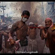 """In this """"Signature Series"""" image by David Longstreath devotees at the Vegetarian Festival in Phuket, Thailand are seen as fireworks expolde around them during a street procession.  The annual festival in Phuket is held on a annual basis and begins usually in late September of early October depending on the lunar cycle."""