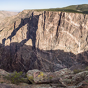 A woman in purple coat admires the gorge at Dragon Point, in Black Canyon of the Gunnison National Park, near Montrose, Colorado, USA. Pressurized molten rock was forced into 1.7-billion-year-old metamorphic rock, forming pink pegmatite stripes on Colorado's highest cliffs. With two million years to work, the Gunnison River and weathering have sculpted a vertical wilderness of rock, water, and sky. This panorama was stitched from 6 overlapping photos.