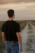 back of a man in a black tee shirt and jeans looking towards a dirt road