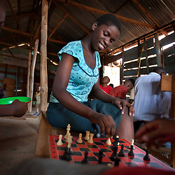 Phiona Mutesi, a 14-year-old chess prodigy, plays chess at the Agape Church inside Katwe, the largest slum in Kampala, Uganda, Dec. 10, 2010. Mutesi lives in the slums of Uganda and is just now learning to read. But her instincts have made her a player to watch in international chess. Mutesi, a naturally talented chess player is coached by Robert Katende of Sports Outreach Ministry. The chess club meets at the Agape Church.