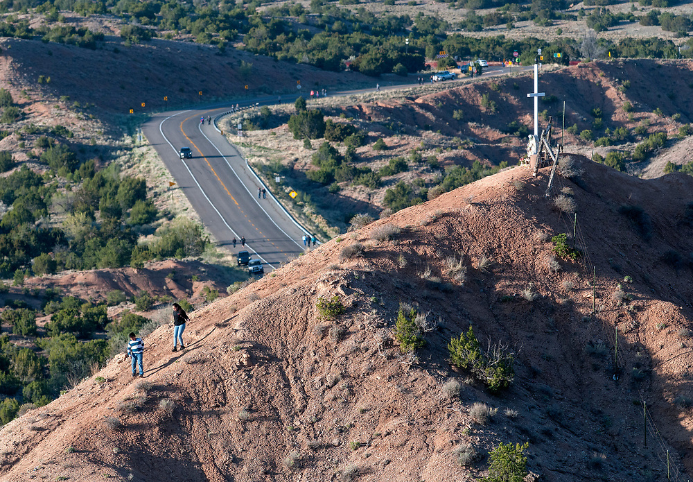 em041417c/a/Juan Diego Morales, 13, left, and Heidi Guillermo, 14, from Albuquerque, walk down from a cross along Juan Madina Road on their way to the Santuario de Chimayo, Friday April 14, 2017. With beautiful weather, thousands of people were making the Good Friday pilgrimage to the Northern New Mexico church.  (Eddie Moore/Albuquerque Journal