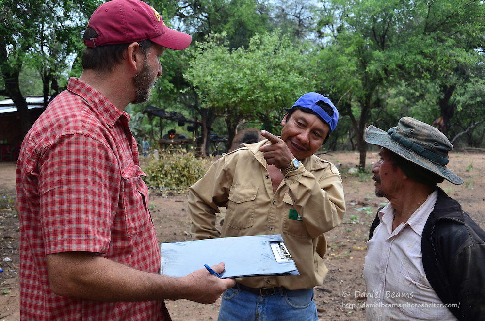 Guarani men talking to development worker