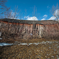 Abandoned sagging barn in a winter field.