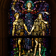In this stained glass image, an angel of the Lord banishes Adam and Eve from the garden of Eden. The window is from the National Shrine of Mary, Help of Christians, known as Holy Hill, in Hubertus, Wis. (Catholic Herald photo by Sam Lucero)