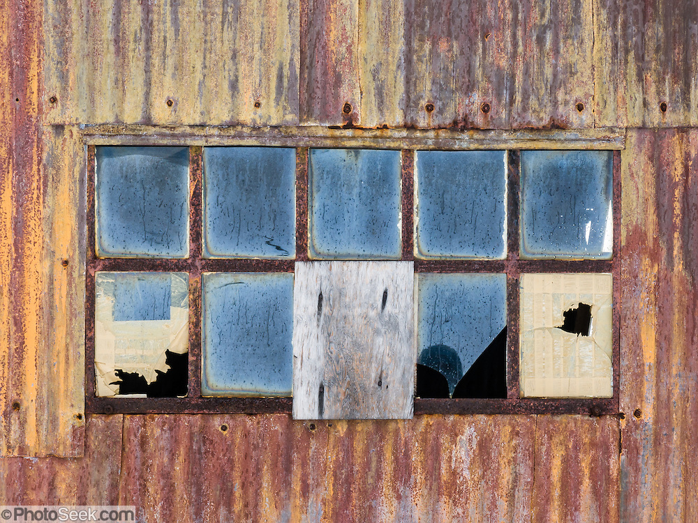 An old broken window and rusted corregated iron siding decay on an island offshore from the Antarctic Peninsula.