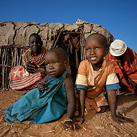 A Samburu family gathers outside their hut as the sun rises
