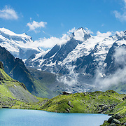 The peaks of Grand Combin (4314 metres / 14,154 feet on left), Combin de Corbassière (center), and Petit Combin (right) rise above Cabane de Louvie hut on Lake Louvie in the Pennine/Valais Alps, Switzerland, Europe.  Optionally stay overnight in dorms at Cabane de Louvie. The dramatic Chamois Path (Sentier des Chamois) starts at La Chaux ski lift and ends at Fionnay PostBus. Cross Col Termin (2648m/8688 ft) in Haut Val de Bagnes nature reserve and descend to Lake Louvie via 1800s stone barns to the north, then to Fionnay (640 m up, 1415 m down in 8.5 hours).