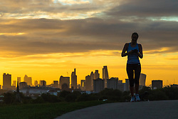 Primrose Hill, London, September 27th 2016. Skyscrapers provide impressive backdrop as a woman jogs on Primrose Hill at dawn in London. &copy;Paul Davey<br /> FOR LICENCING CONTACT: Paul Davey +44 (0) 7966 016 296 paul@pauldaveycreative.co.uk