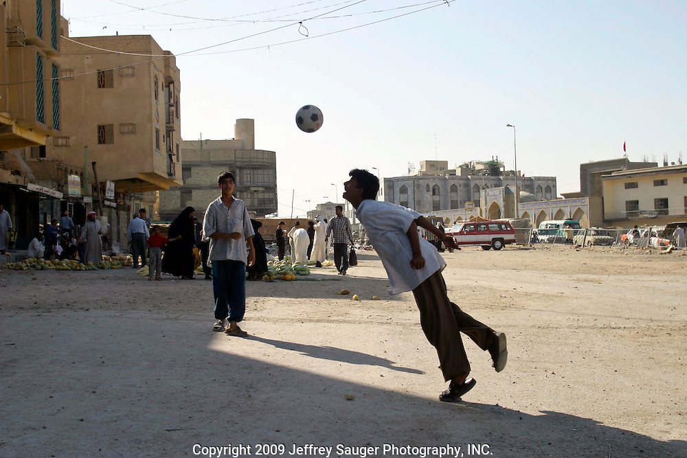 Iraqi Shiite boys play soccer near the market in Karbala, Iraq, Wednesday, July 23, 2003. Models of self-determination, Shiite controlled areas like Karbala are safer and starting to thrive more than under Saddam Hussein's regime. As the Shiite spiritual leader Ayottallah Ali Sistani has told his people to have patience with America, their patience is wearing thin with what they perceive as an occupation.